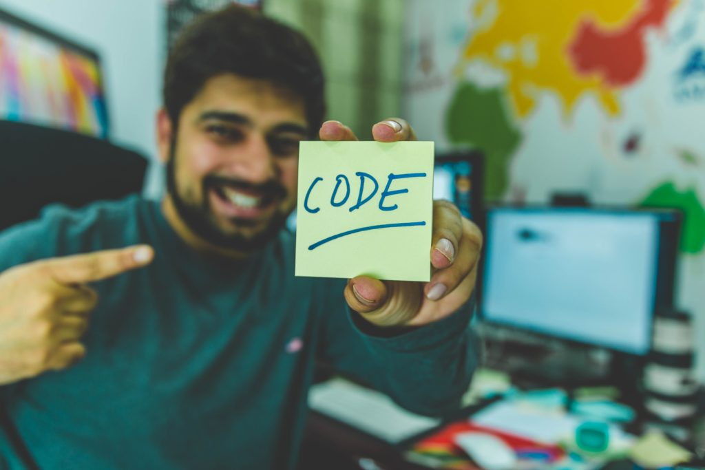 man with sticky note that says code