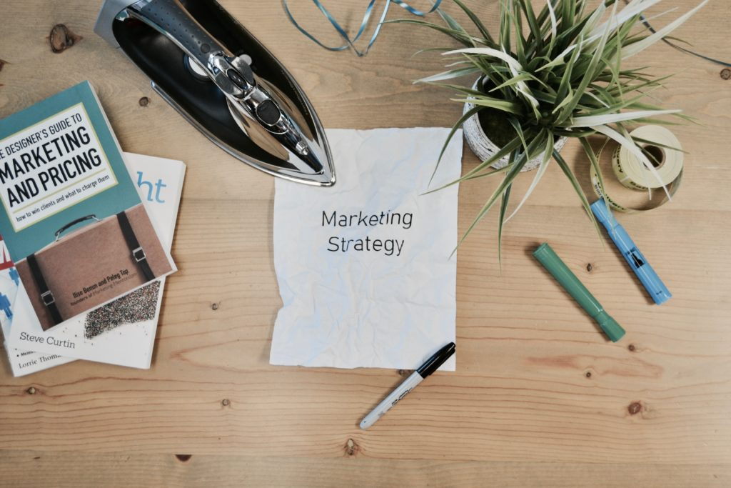 paper that says marketing strategy next to books and pencil