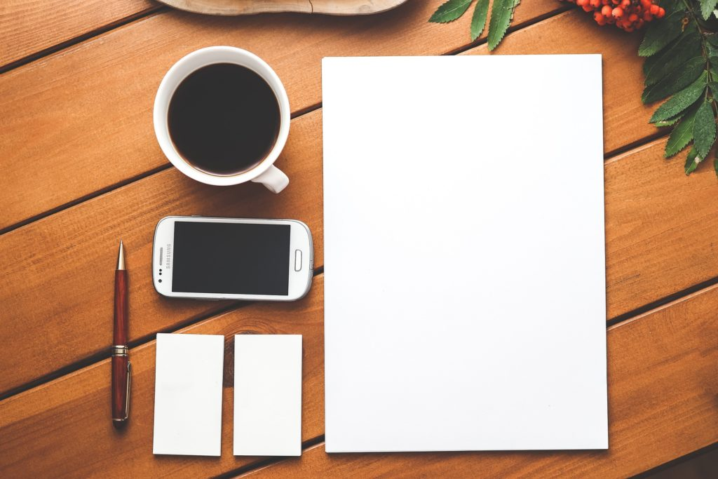 Blank document on table with coffee and smartphone