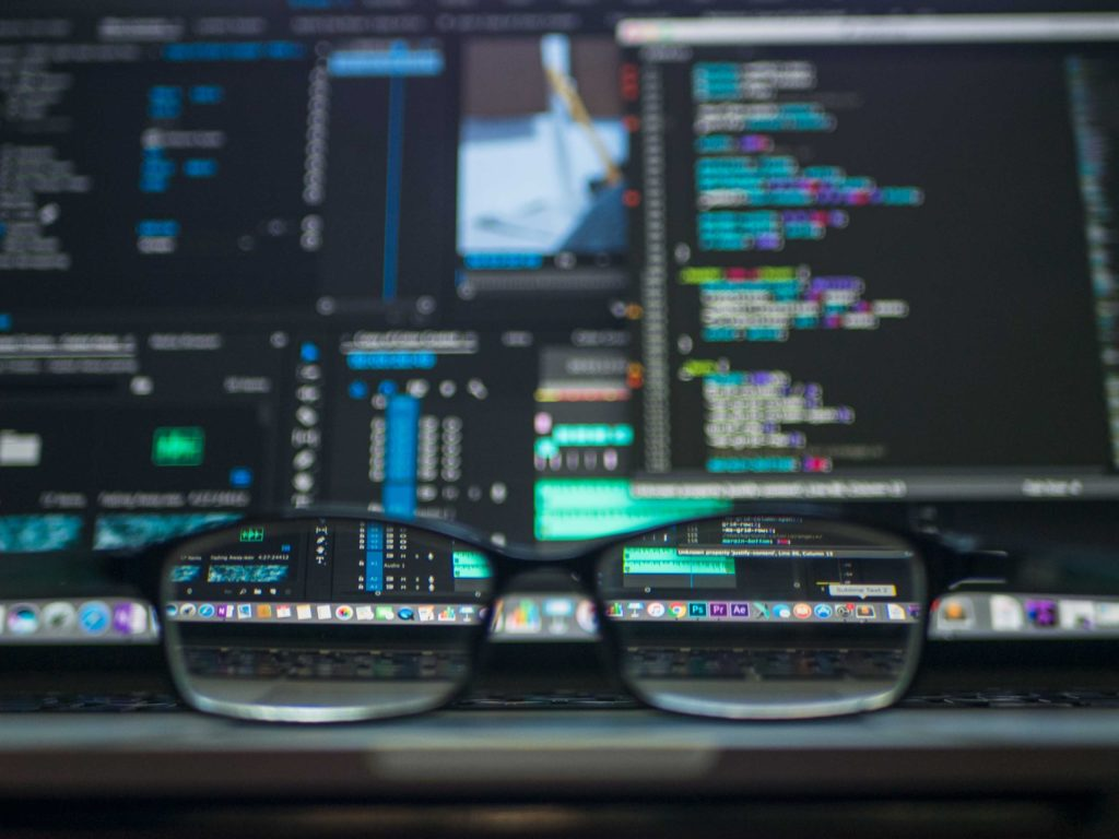 glasses on desk with code on laptop screens