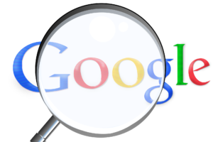 magnifying glass hovering over google logo
