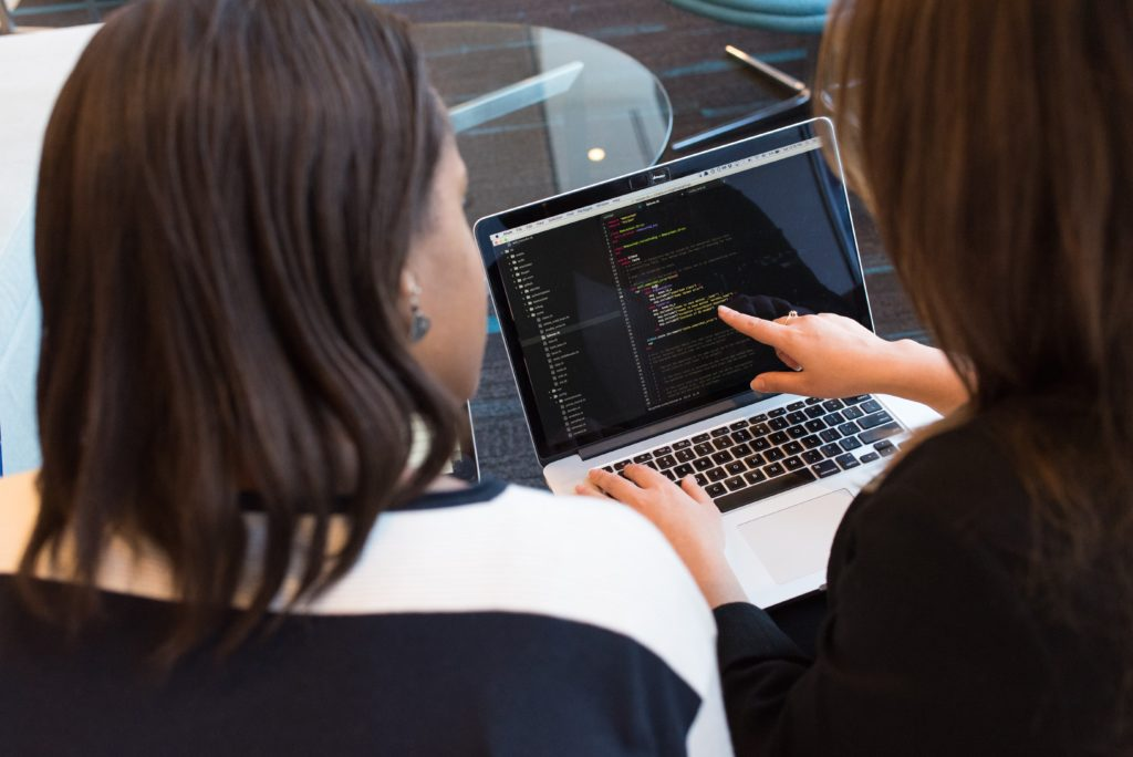 two women looking at code on laptop