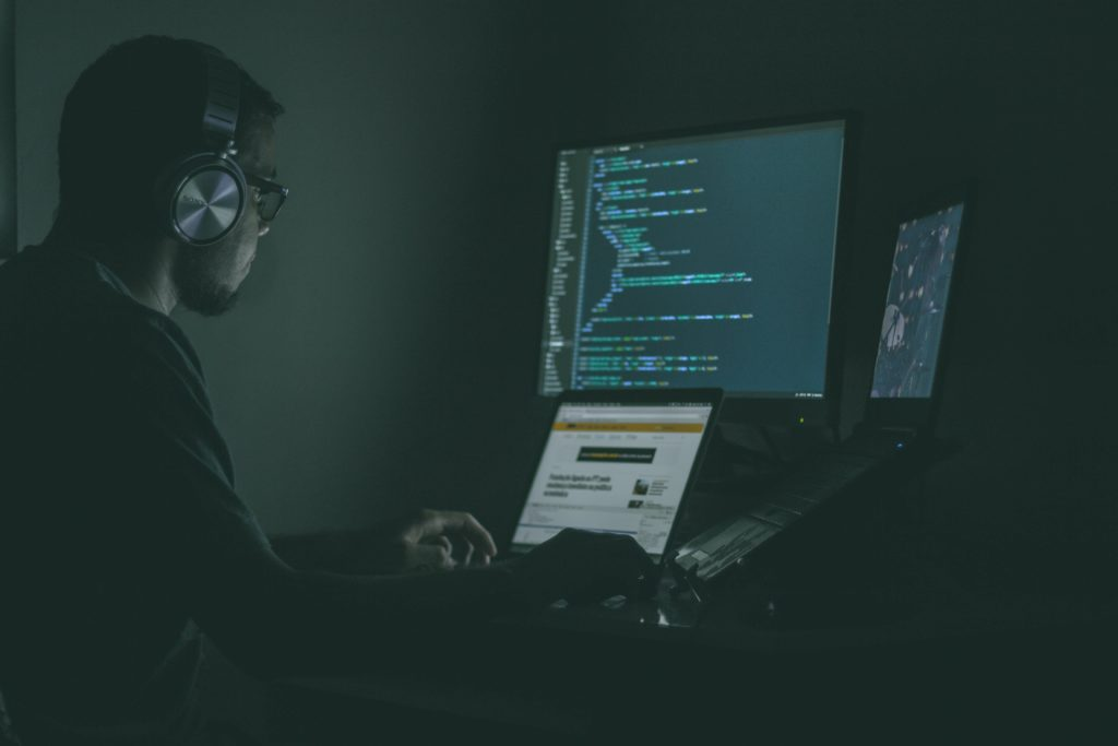 man in dark on computer coding
