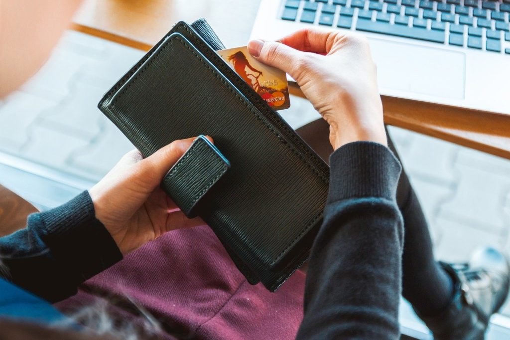 person with wallet making online purchase