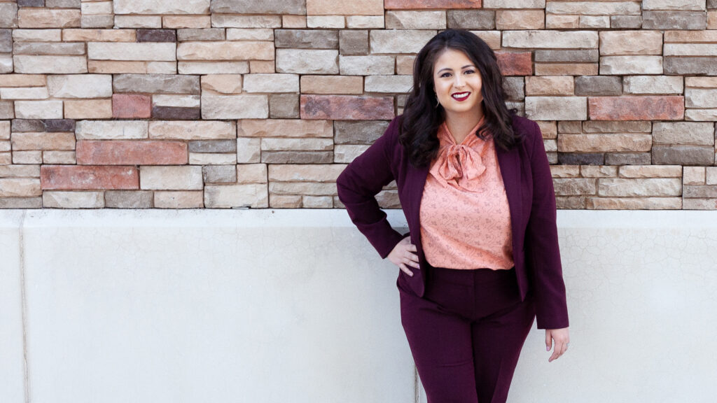 female lawyer standing against brick wall with hand on hip